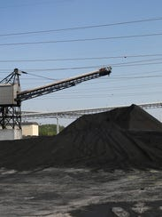 Large piles of coal brought in by railroad cars wait