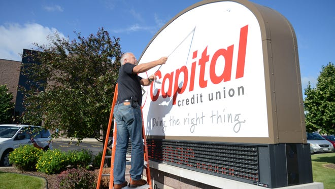 In this file photo from 2014, Capital Credit Union CEO Tom Young unveils updated signage at the credit union's Ashwaubenon headquarters. In 2014, Capital Credit Union was formed when Pioneer Credit Union and Kimberly Credit Union merged.