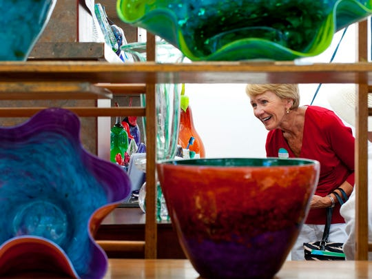 Elaine Ward, a seasonal Naples resident, looks at Stephen R. Nelson's glasswork at a booth at the Naples National Art Festival on Feb. 23, 2014.