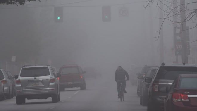 A bicyclist rides through heavy fog in York in this 2016 file photo.
