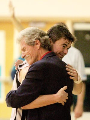 Head coach Roger Raymond embraces team captain Cole Stretton at the end of Friday's easy 85-72 win over Oasis Charter.