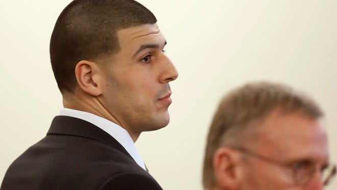 Former New England Patriots football player Aaron Hernandez listen during his murder trial.