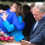 David Jacoby reaches out to his brother's casket while his wife Kendra Jacoby receives a hug during a celebration of life for John Jacoby Friday, May 22, 2015, at Lakeview Cemetery in Windsor, CO.