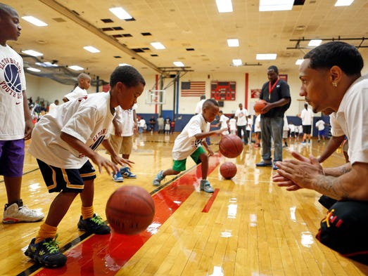 Daquan Brickhouse, right, a former Peekskill High School player and current Coppin State player, works with kids on dribbling at the Elton Brand youth basketball clinic, Aug. 2, 2014 at Peekskill High School. Brand, a Peekskill High School star, is a free agent and is in the twilight of his NBA career.