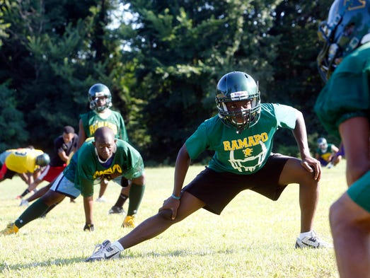 Senior Jeremy Rameau, 17, stretches during the first day of football practice at Ramapo High School in Spring Valley Aug. 18, 2014.