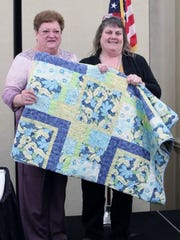 Quilt maker Marlene Schulte (left) with raffle winner Pam Baese.