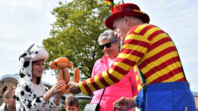 Bobo the Clown hands Bella Souza, 9, a balloon monkey, while dressed in her cow costume during the 2018 harvest festival.