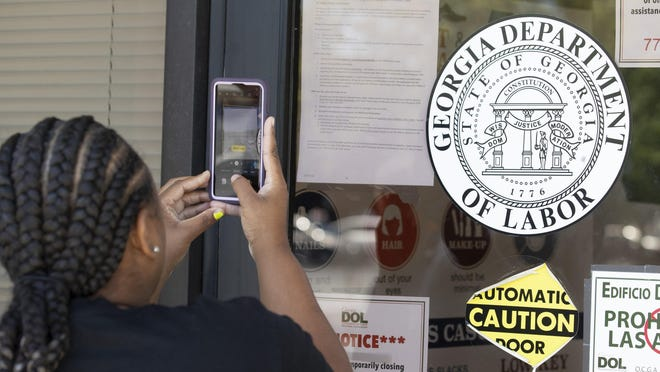 Arnashia McCain uses her phone to copy phone numbers posted on the locked doors of a Georgia Department of Labor office Thursday, May 7, 2020, in Norcross Ga. McCain, who said she drives for Lyft and has had her hours cut in her job in retail, has been unable check on the status of her her unemployment claim.