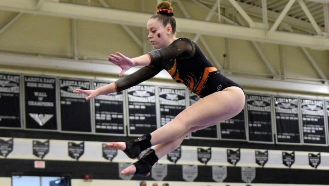 Casey Gittelman of Anderson comes high off the balance beam with full concentration.