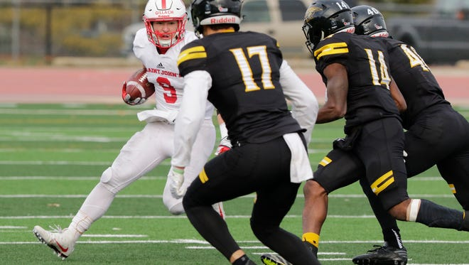 St. John's wide receiver Will Gillach tries to pick up yardage in his team's 31-14 second-round playoff loss to Wisconsin-Oshkosh Saturday afternoon at Titan Stadium in Oshkosh, Wis.
