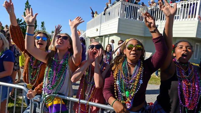 Revelers shout for beads Sunday during the Krewe of Wrecks Pensacola Beach Mardi Gras Parade.