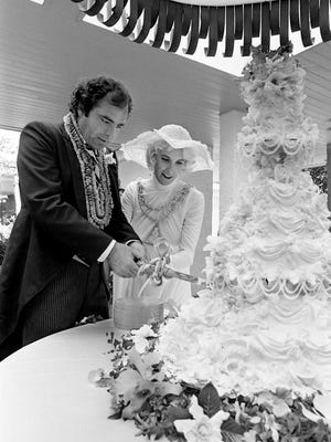 Nashville real estate executive Michael Tomlin, left, and his bride, Tammy Wynette, are cutting their wedding cake during their reception after getting married on the grounds of her Franklin Road home July 18, 1976.