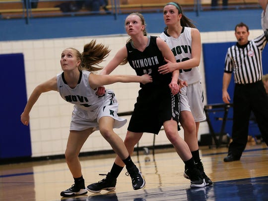 Plymouth senior Alexa Ebeling (middle) vies for a rebound against Novi players during Monday's game.