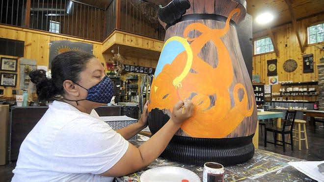 Gigi Obringer works on her rain barrel at Tin Can Chandelier on Thursday.