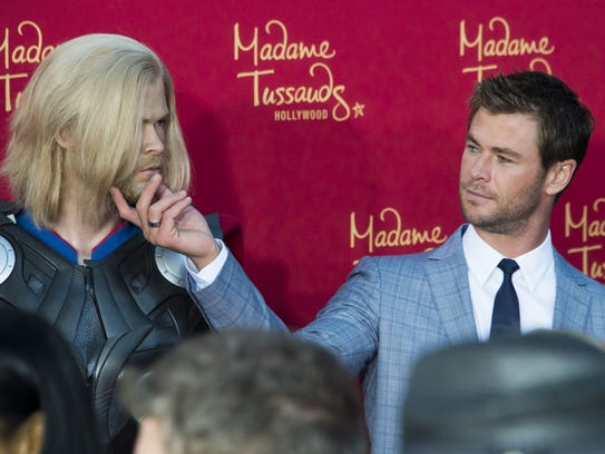 Chris Hemsworth, right, takes a close look at a figure