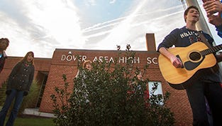 Leon Zellers, age 16, plays guitar while Zach Schriver, age 14, helps with the music during See You at the Pole at Dover High School Wednesday, September 25, 2013