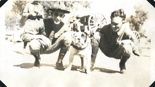Two Battery A soldiers posing with Peanuts, CAC's bulldog mascot that traveled across the United States with the unit.
