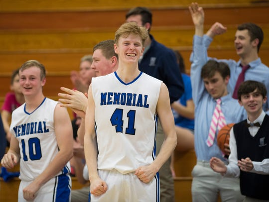 Memorial's Sam Devault (41) and Michael Lindauer (10) celebrate a three-pointer against North at Memorial High School last season.