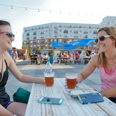 Leslie McGowan (left) and Annette DeBastiani, both of Wilmington, share a table as they hang out following a yoga class at Constitution Yards beer garden at the Wilmington Riverfront.
