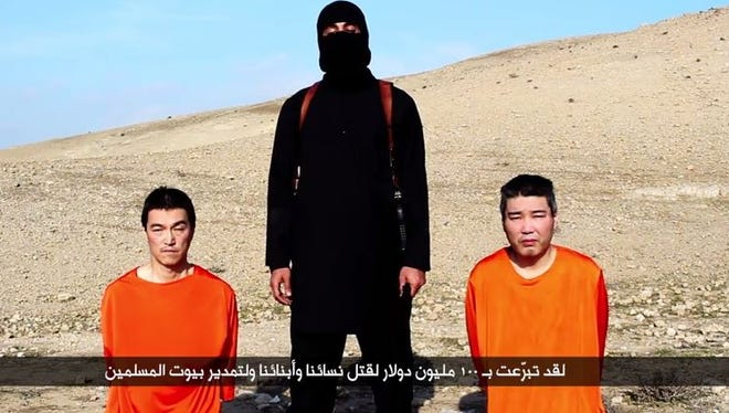 This screen grab from a YouTube video purporting to be from the Islamic State  shows a militant with two men who appear to be Japanese hostages.