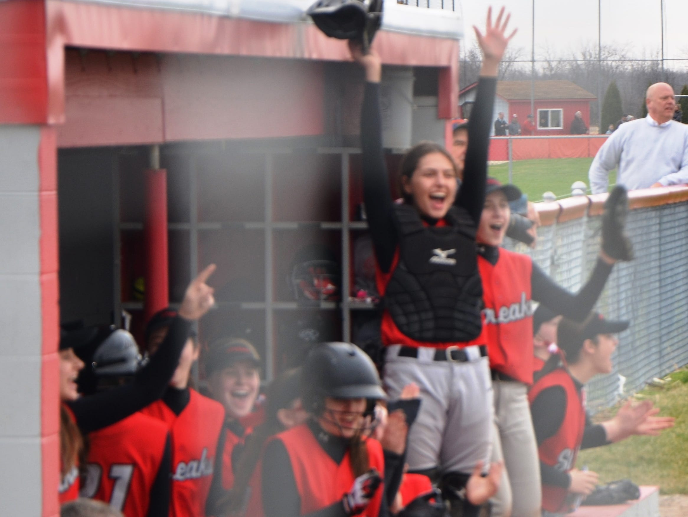 The St. Joseph Central softball team celebrates from its dugout as a run scores for the Crimson Streaks against Clyde High School. SJCC won the game 4-2. Rich McGowan/News-Messenger