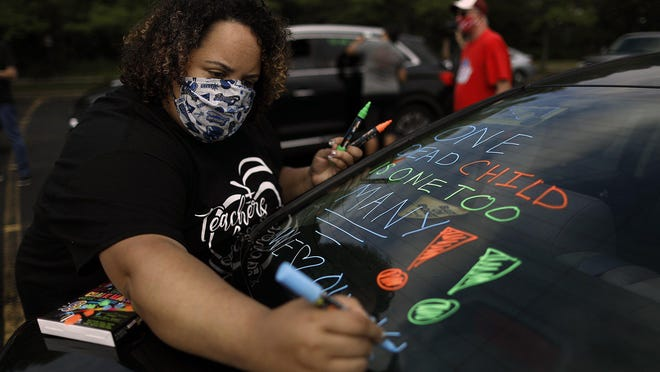 Kelsey Burkett, a choir teacher at Hilliard Memorial Middle School, decorates her car at a parking lot in Columbus, Ohio, on August 3, 2020.  A group of around 20 teachers participated in a caravan that went past several prominent buildings in Downtown Columbus, to urge public officials to reverse their plans to welcome students back for in-person learning in the fall.