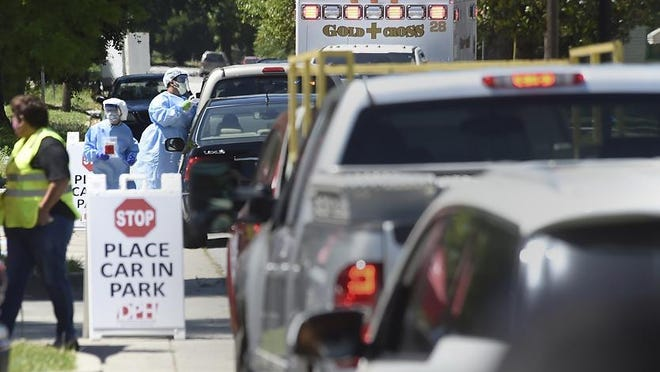 Medical personnel, left, conduct drive-up coronavirus testing outside Fire Station 1 in Augusta Wednesday afternoon May 6, 2020.