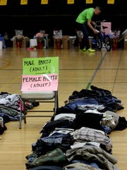 Gifts and food for Greenfield School District families circle a Greenfield High School gym with lines of sorted folded clothing in the center during the 2014 Holiday Sharing Initiative.