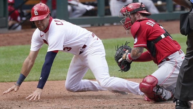 St. Louis Cardinals outfielder Dylan Carlson, left, is tagged out at home by Cincinnati Reds catcher Tucker Barnhart during the fourth inning of a game on Sunday, Aug. 23, in St. Louis.