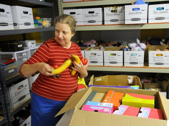 Nelda Jenkins unpacks plastic fruits in the toy room at the new location of the Christian Service Center.