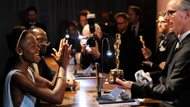 Lupita Nyong'o, winner of the award for best actress in a supporting role for '12 Years a Slave,' applauds after getting her award engraved at the Governors Ball after the Oscars.