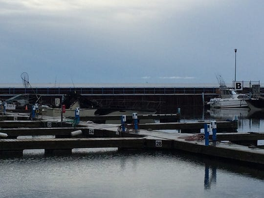 Three boats are underwater and fire damage can be seen to two vessels docked in the Algoma Marina on Thursday.