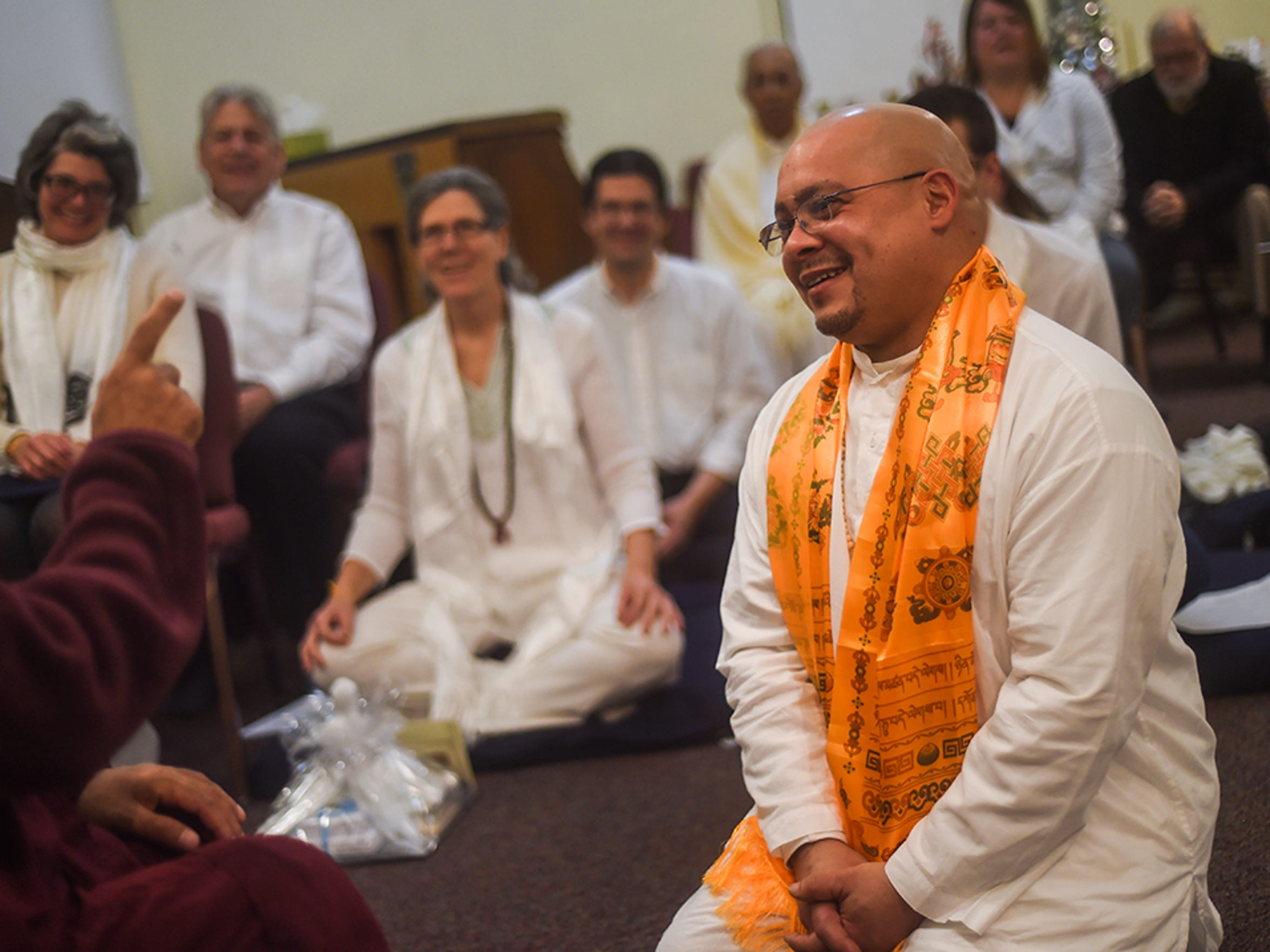 Angel Correa smiles while listening to Bhante Sujatha during a ceremony Dec 7, 2014, where Correa took his Buddhist Upasaka precepts. The precepts are a Buddhist concept that requires commitment to refraining from killing, stealing, conducting sexual misconduct, false speech and drug use.