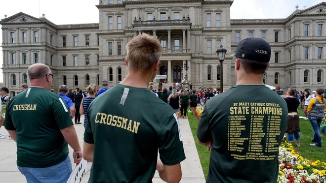 St. Mary's Catholic Central player Brendan Walters (right), wearing the 2019 State Championship T-shirt, attends the #letthemplay rally at the state capital Friday with teammate Riley Crossman. They traveled to the event with Riley's parents Kyle (left) and Cindy Crossman and younger brother Roman, who plays for the junior varsity team.