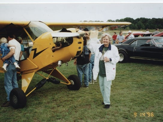 Lois Moore stands next to a Piper Cub at an air show