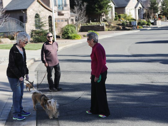 Bonnie Smith, right, talks to her neighbors Wendy and Paul Gervasi while walking her dog Pistol on Thursday afternoon in her neighborhood.