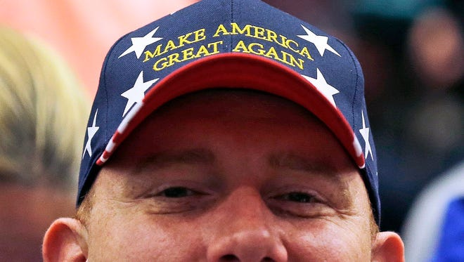 "Allan Hale of Little Rock, Ark., who is active duty with the U.S. Navy based at the submarine base in Groton, Conn., wears a ""Make America Great Again"" hat while waiting for the arrival of Republican presidential candidate Donald Trump before a campaign event at Crosby High School in Waterbury, Conn., Saturday, April 23, 2016. (AP Photo/Charles Krupa)"