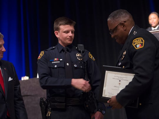 Montgomery Police Officer A.C. Smith receives the combat star from Montgomery Police Chief Ernest Finley Jr. during the Montgomery Police Department Police Memorial Day Service on Thursday, May 21, 2015, in Montgomery, Ala.