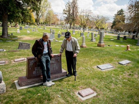 In this April 9, 2015, photo, cousins Merlin Morrison, 80, and John Arling Morrison, 84, talk at the gravesite of their grandparents John G. and Marie Morrison in the Salt Lake City Cemetery. Industrial Workers of the World songwriter Joe Hill was convicted of the Jan. 10, 1914, murder of John Morrison and executed at the Utah State Prison.