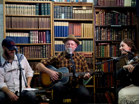 In this May 23, 2015, photo, Duncan Phillips, center, performs a song by songwriter Joe Hill along with Morgan Snow, left, and Kate MacLeod at Ken Sanders Rare Books in Salt Lake City. The event raised funds for a Joe Hill memorial concert planned for September in Sugar House Park. Hill was executed in Utah on Nov. 19, 1915, after being convicted of a murder many people believe he did not commit.