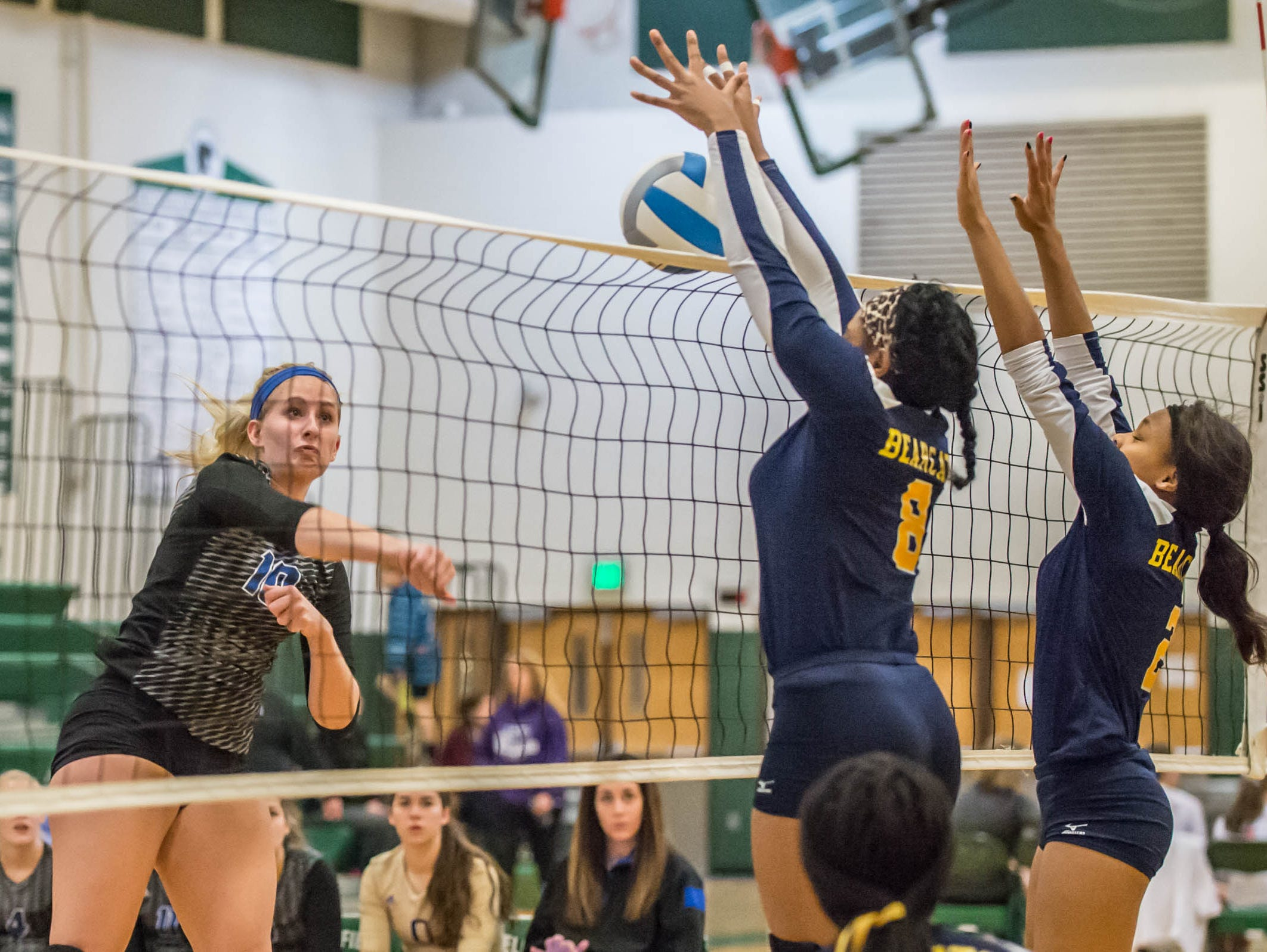 Battle Creek Central's Jamesha Smith (8) and Eirion Traylor (2) go for the block over Harper Creek's Olivia Leson (10) at the All-city volleyball tourney on Saturday.