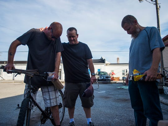 Gary Singer, middle, prays with a man in downtown Hanover Thursday Sept. 24, 2015 while giving free hot dogs and bottled water to residents. Singer started Jeremiah's Garage in July as a Christian community outreach ministry to help those struggling with life problems such as addiction.  Singer suffered from alchoholism and homelessness in his past but since being sober for four years was inspired to start Jeremiah's Garage to help those who might find themselves in similiar situations.