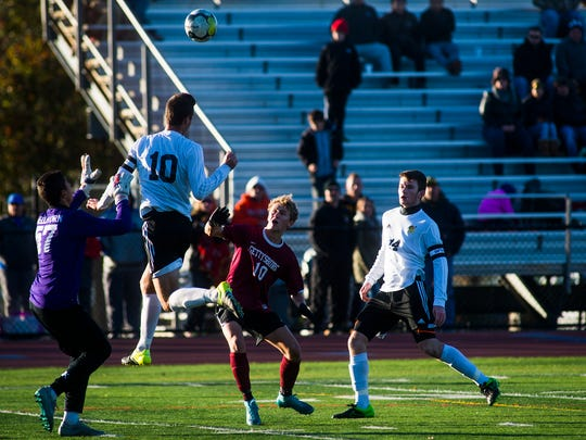 Gettysburg's Adam Yingling keeps his eye on the ball after Northwesten Lehigh's Jonathan Blaine deflects the ball away from the goal during Saturday's PIAA Class AA boys' soccer quarterfinal.
