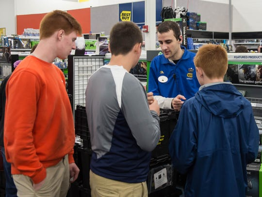 Best Buy associate Justin Davis assists customers with video game questions on Friday at Best Buy in Battle Creek.