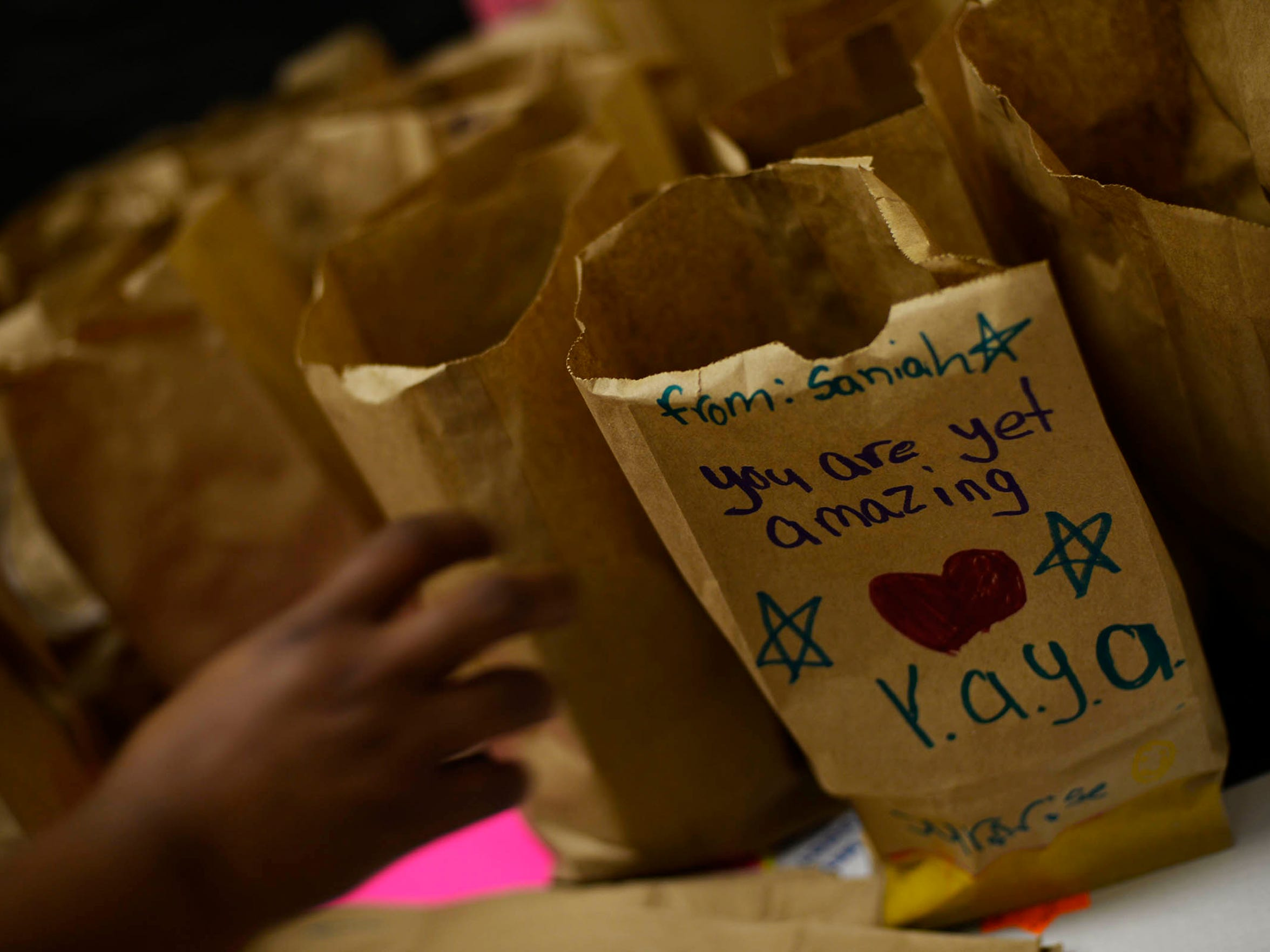 Paper bags decorated and filled with a sandwich and snacks by seedlings, ages 5-7, are prepared to be taken to Bell Socialization women's shelter during a YAYA Girls meeting at Helen Thackston Charter School in York in November. The month was filled with small community service projects like this to teach the girls the importance of giving back.