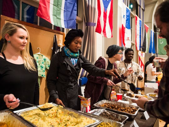 Justina Moloawu, a junior at Gettysburg College and a native of Nigeria, serves chicken curry for guests Saturday Dec. 5, 2015 during BurgBurst at Gettysburg College. The event celebrates the diversity of the student campus with international cuisine, performances and fashion.
