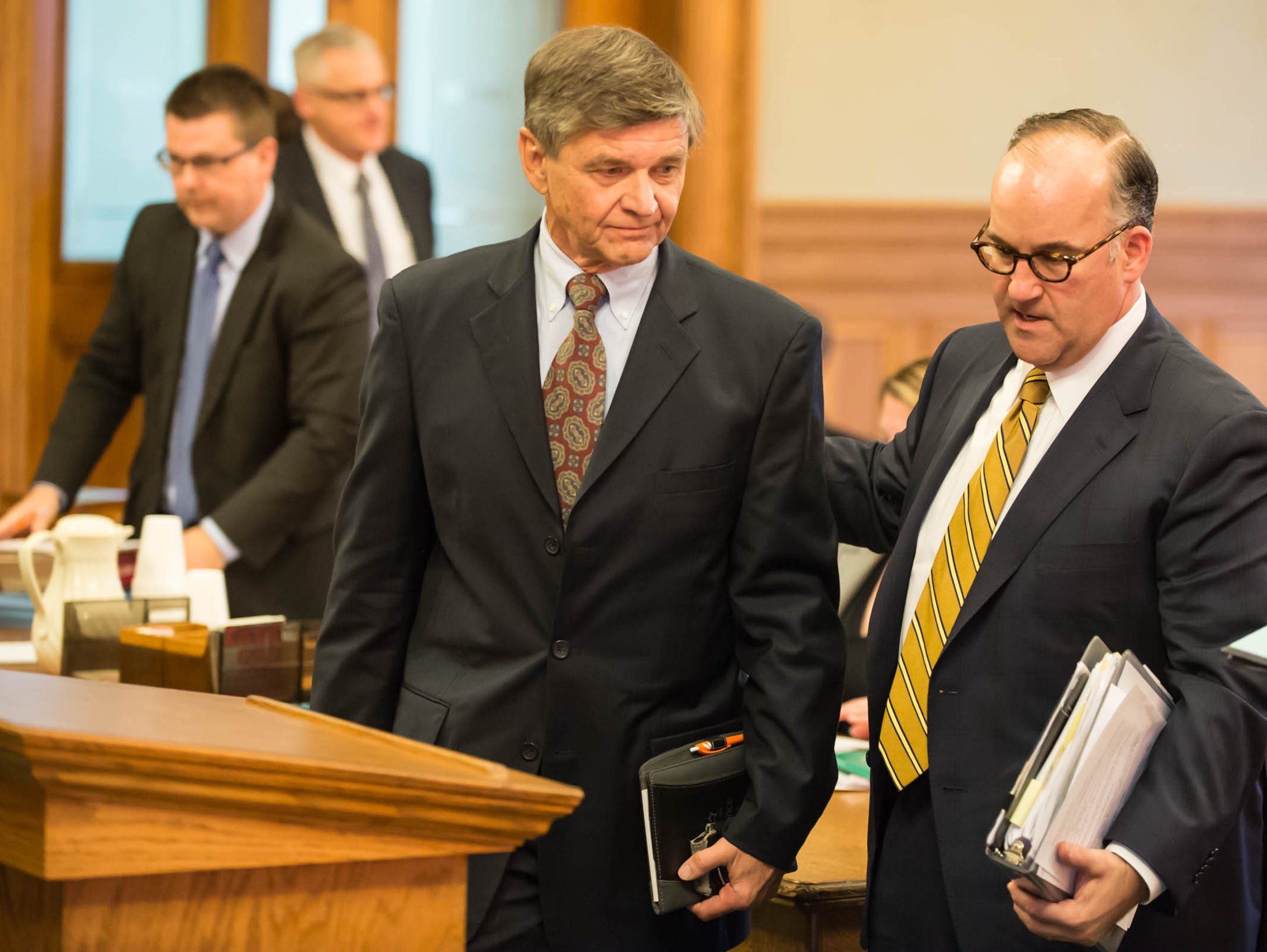 In 2015, former Summit Pointe CEO Erv Brinker walks up to the podium with one of his attorneys, Matthew Vicari, as he prepares to plead guilty to Medicaid fraud and embezzlement charges in Ingham County Circuit Court's Mason courthouse.