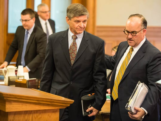 In this November photo, former Summit Pointe CEO Erv Brinker walks up to the podium with one of his attorneys, Matthew Vicari, as he prepares to plead guilty to Medicaid fraud and embezzlement charges in Ingham County Circuit Court's Mason courthouse.