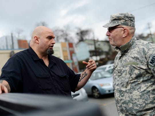 John Regelman, right, talks with John Fetterman, offering