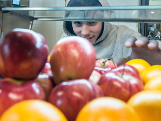 Pennfield High School freshman Brendan Pond goes for an apple during a recent lunch.